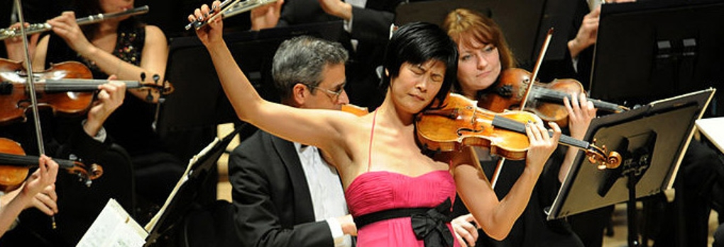 A violin soloist sweeps the bow high off the strings while the orchestra plays behind her