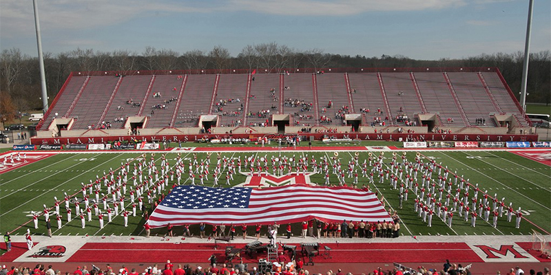 The Miami University Marching Band performs on the Yager Stadium field, unfurling a large American Flag