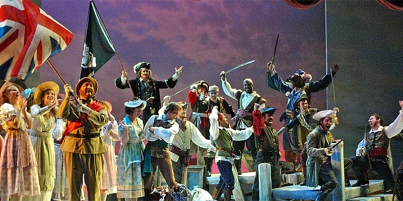 The costumed cast of Pirates of Penzance sing jubilantly, as characters hoist flags and swords
