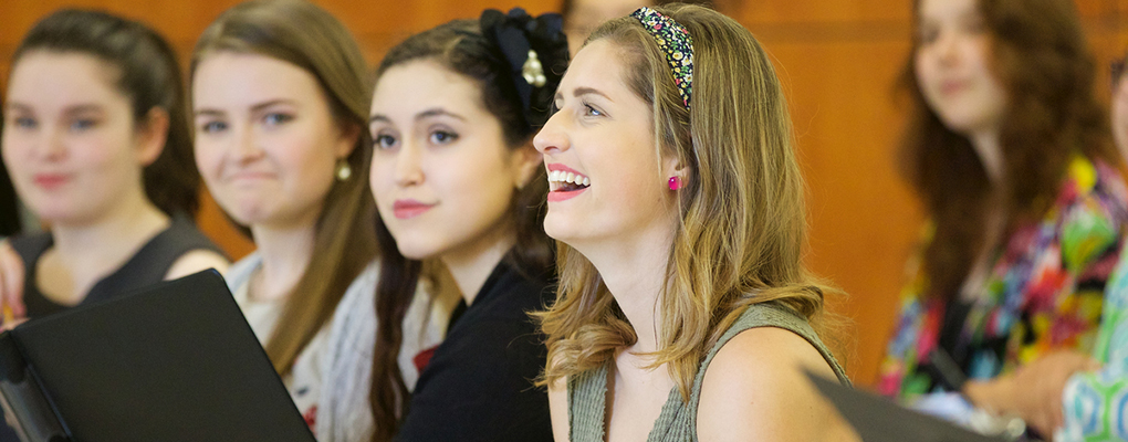 A row of students laugh at a joke