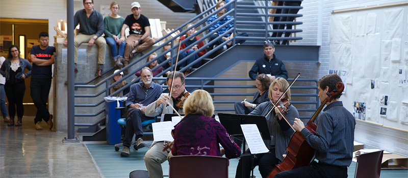 A faculty string quartet performs an impromptu concert at Alumni Hall as passersby listen