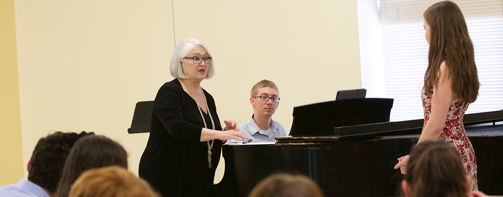 An instructor stands near the piano and offers advice to a vocalist