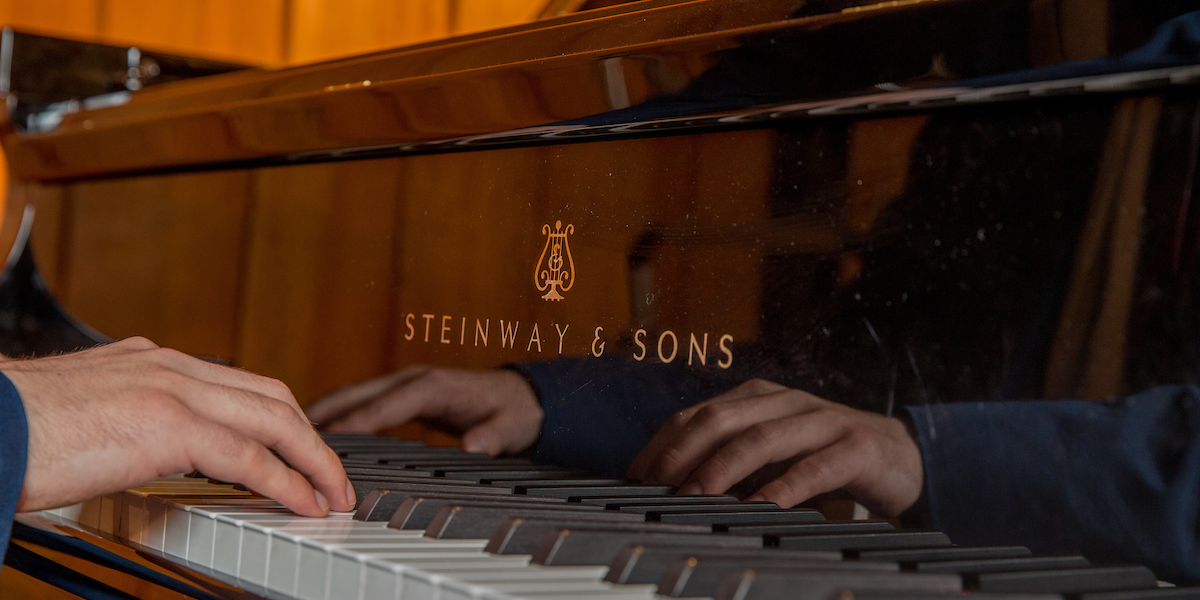 Hands on a keyboard are reflected against the mirrored surface of the Steinway grand piano