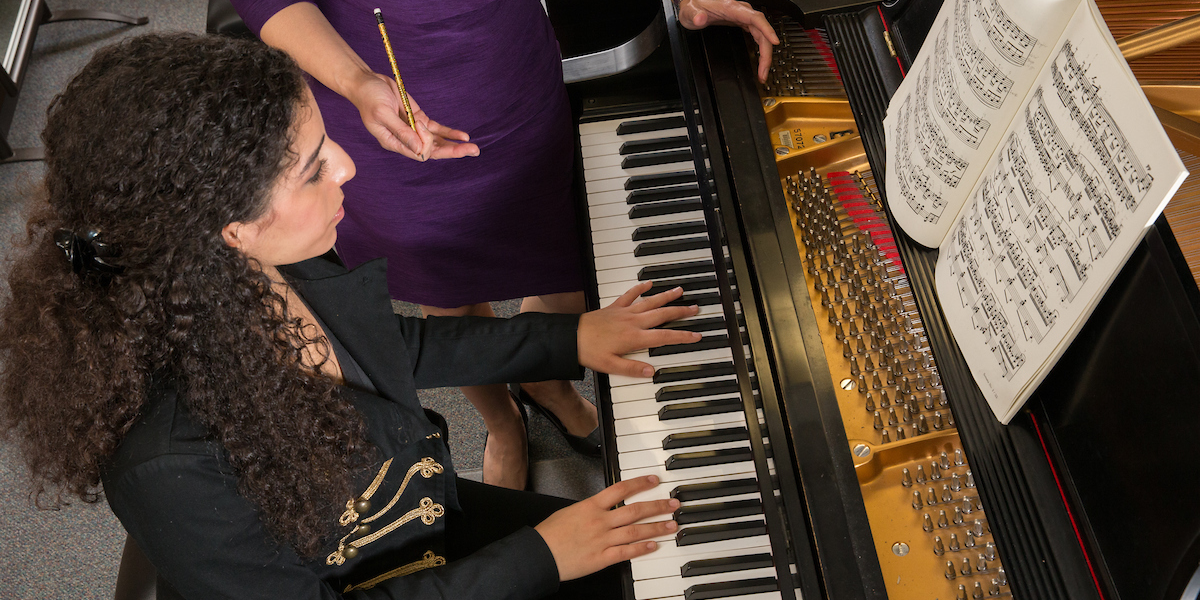 A student is seated at the piano, with music on the rack, as her teacher guides her from the side during a lesson