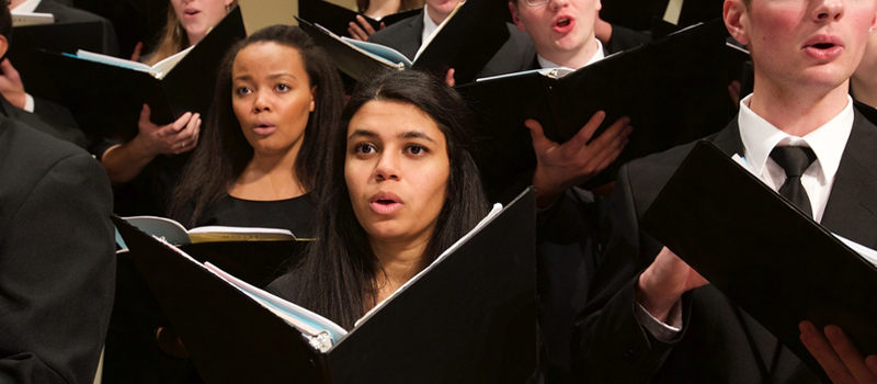 Closeup of a section of singers in a Glee Club Collegiate Chorale joint concert