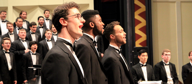 Side view of 3 male soloists at a Glee Club concert
