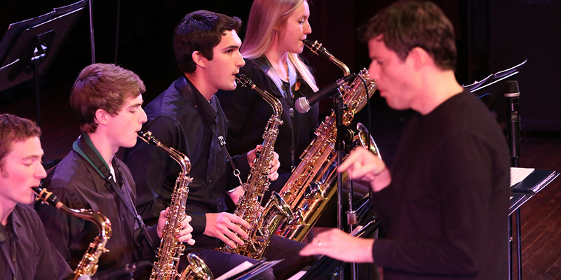A row of saxophone players perform at the Jazz Ensemble concert