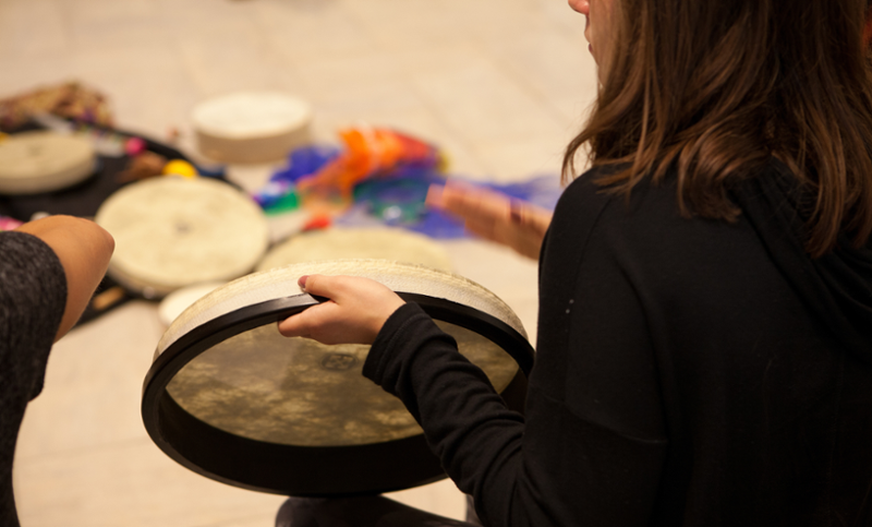 Hand drums are arranged on the classroom floor in the background. Seen from behind, a  student plays a flat-style drum in the foreground.
