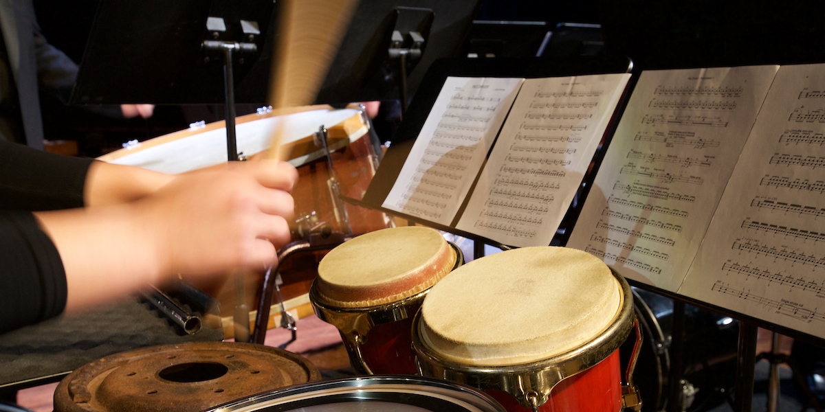 A performer uses sticks to play a drum kit at Percussion Ensemble concert