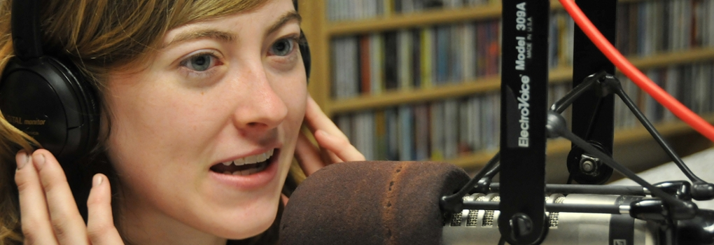 Woman holding her fingers to the sides of her headphones speaks into a broadcast microphone