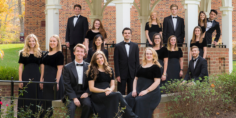 Chamber Singers pose in concert attire near a gazebo in Fall 2016