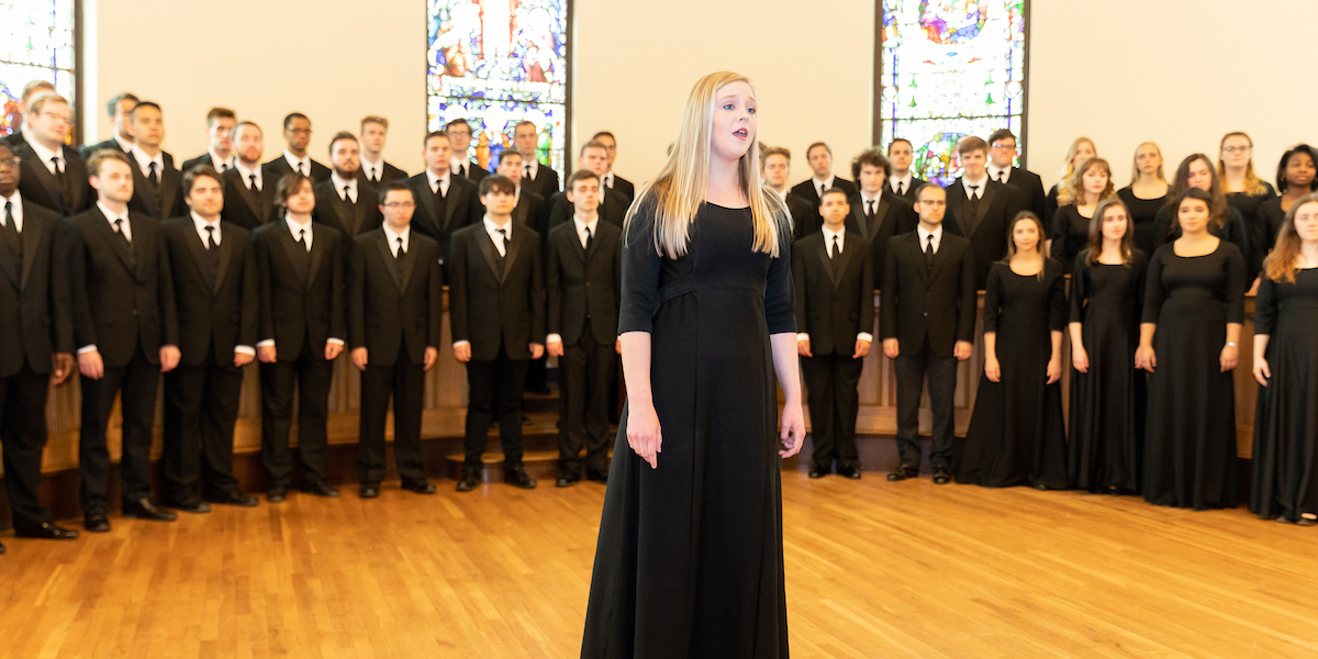 A soloist stands apart from the Chorale as she sings in Kumler Chapel