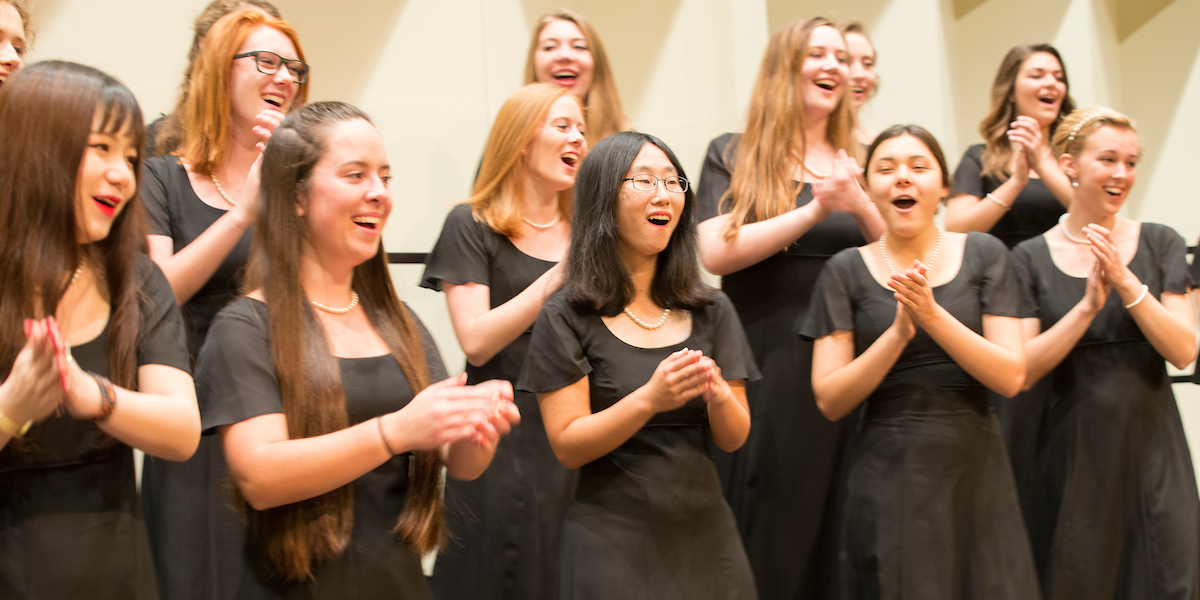 A group of smiling and clapping Choraliers in concert