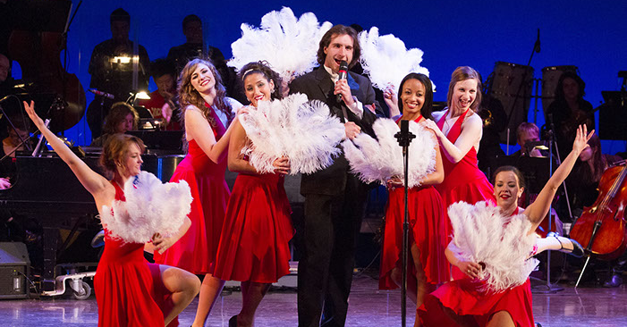 A man holds a microphone and sings, surrounded by dancers in red dresses and white feather fans during a fundraiser concert