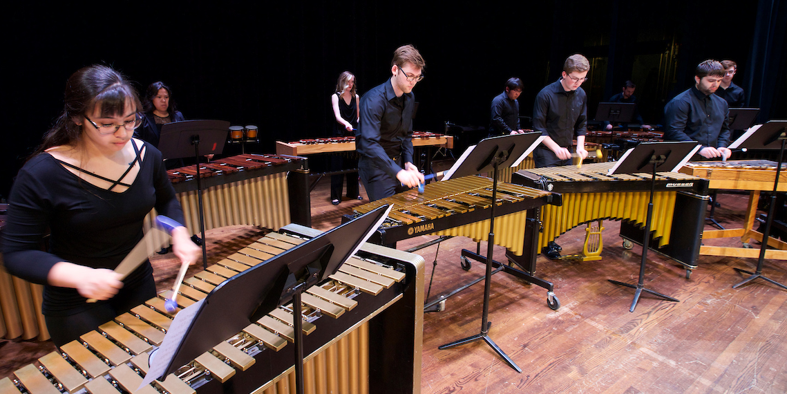 Percussion ensemble members play on a row of marimbas in concert