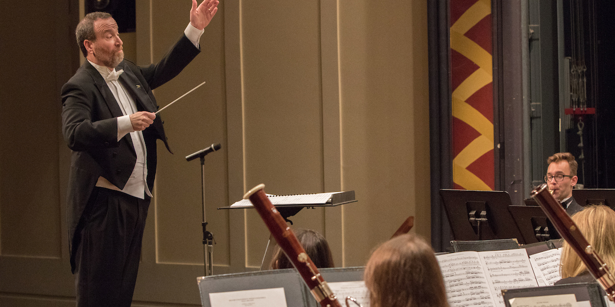 As seen from within the ensemble, the conductor lifts his hand to give a cue. Bassoonists are visible in front.