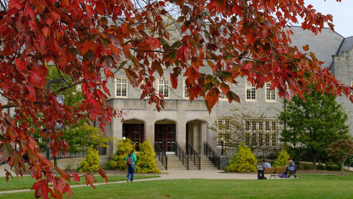 A student walks near Presser Hall, as red autumn leaves frame the image