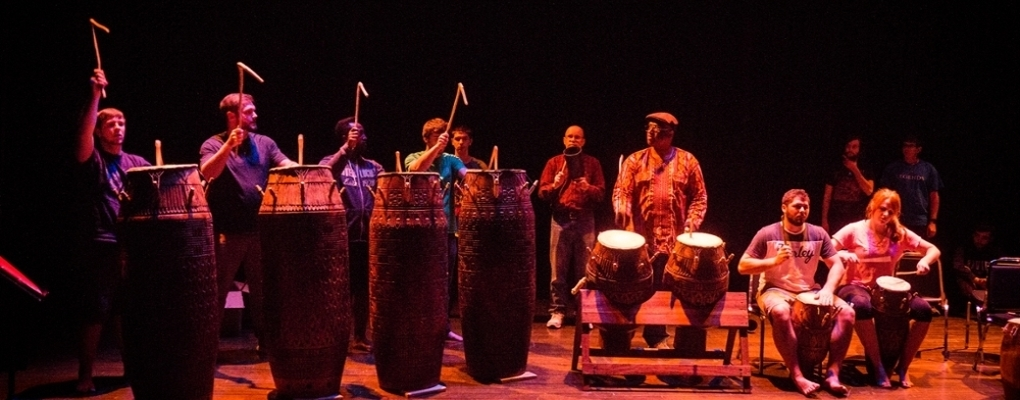 Performance of world music on drums and other percussion instruments. Performers are holding high bent drumsticks