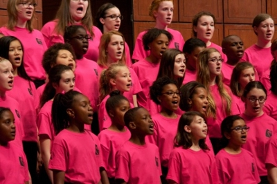 Wearing matching red t-shirts, children on risers sing at a performance of the Cincinnati Childrens Choir