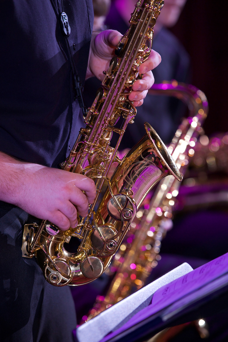 Closeup of an alto sax, with other musicians visible in background