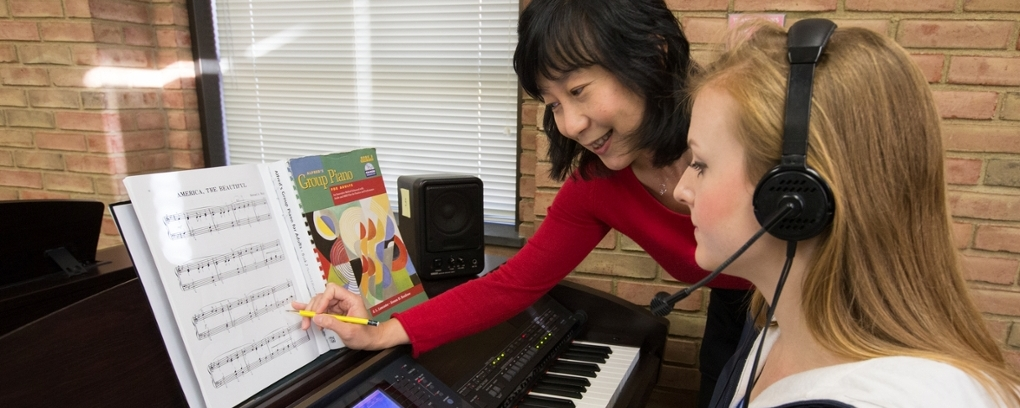 Dr. Tan works with a student in piano class