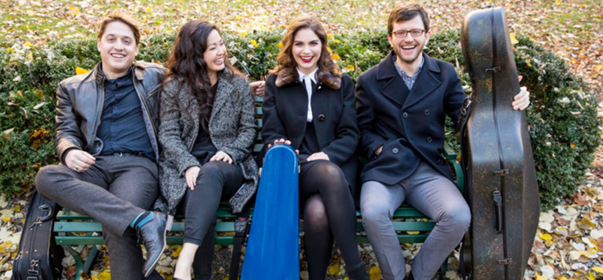 Four people smiling sitting on a bench