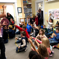 Kevin Spencer teaches a magic trick to children at McGuffey Montessori