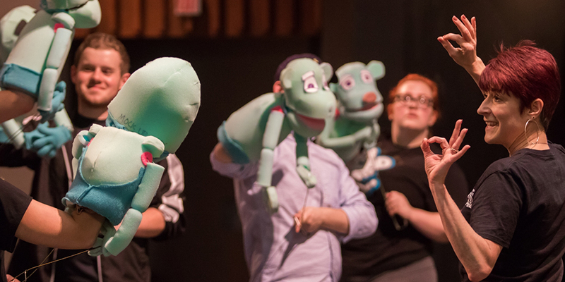 Actors and puppets receive direction during a rehearsal of Avenue Q
