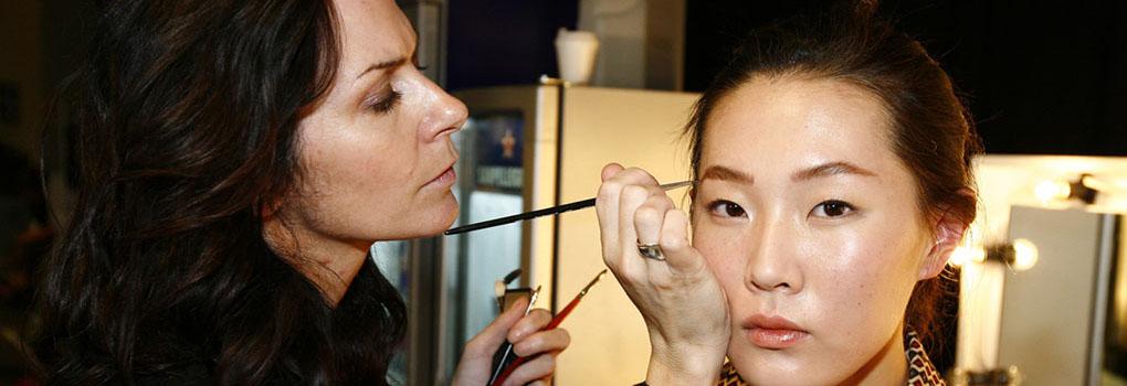 A makeup artist applies makeup to an actress