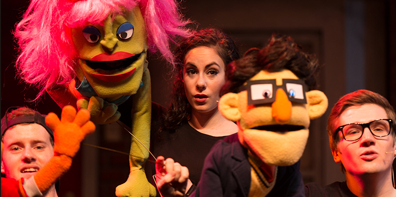 A puppeteer between 2 puppets from the production of Avenue Q