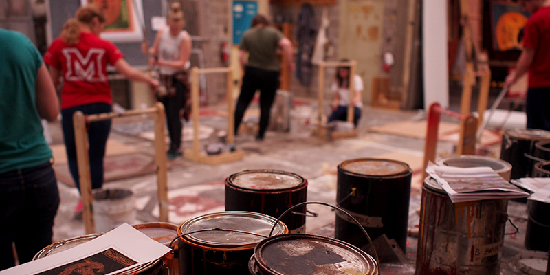 Cans of paint in foreground, with students painting scenery in background