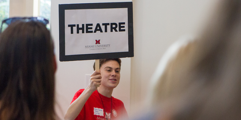 A student holds up a sign to gather people who are interested in learning more about the Theatre program during an Arts Day event