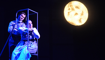 Actors perform in front of moon