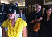 An AIMS student uses a virtual reality headset as bystanders watch