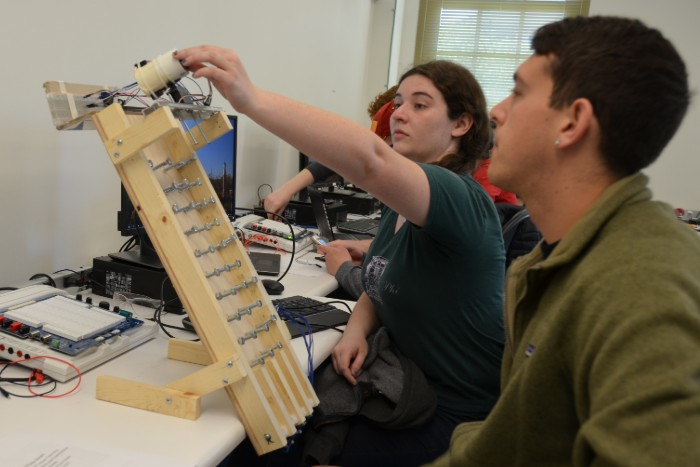Two students working on a plinko-like construction
