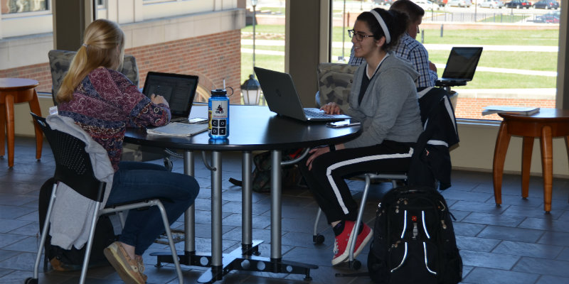 Two female students working in a common area Garland Hall