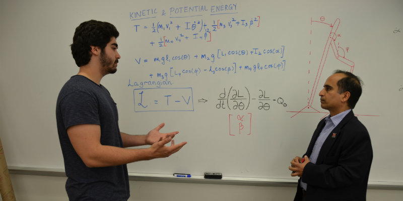 Dr. Shukla and his grad student at a white board. They are looking at equations to help them solve a problem