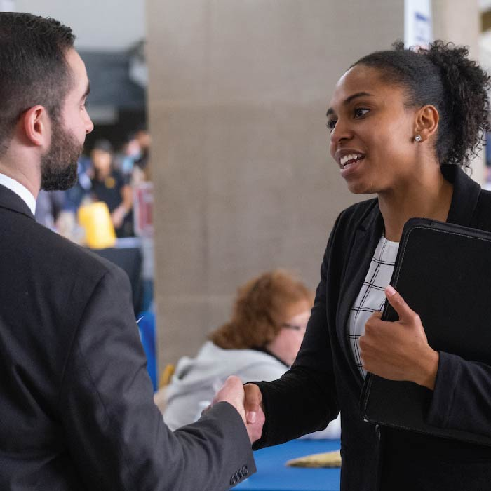 Woman in a suit shakes hands with a male, also in a suit.