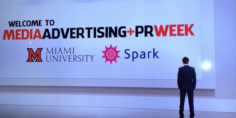 Student standing in front of welcome sign for Media Advertising and PR Week at Miami University.
