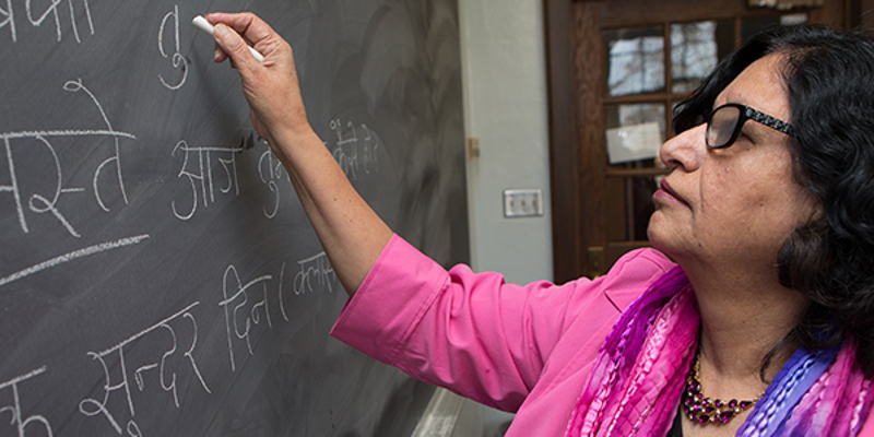 Faculty member writing in Hindi on chalkboard.