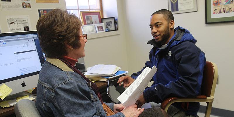 advisor conversing with student