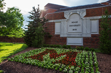 Photo of Miami University's 1809 insignia wall with 'M' flower bed