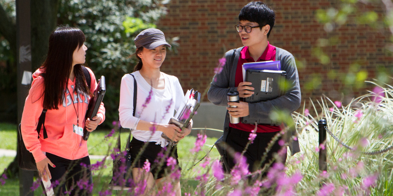 Three international students walking on sidewalk and speaking to each other.