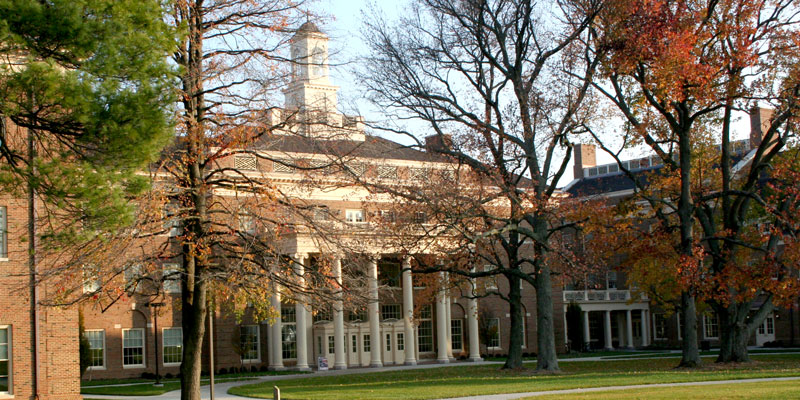 Farmer School of Business exterior in the fall. Large building with clock tower and pillars over the entrance surrounded by trees turning orange.