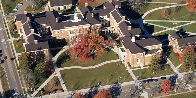 Aerial shot of Farmer School of Business in the fall. Viewed from above, a brick building surrounded by fall foliage.