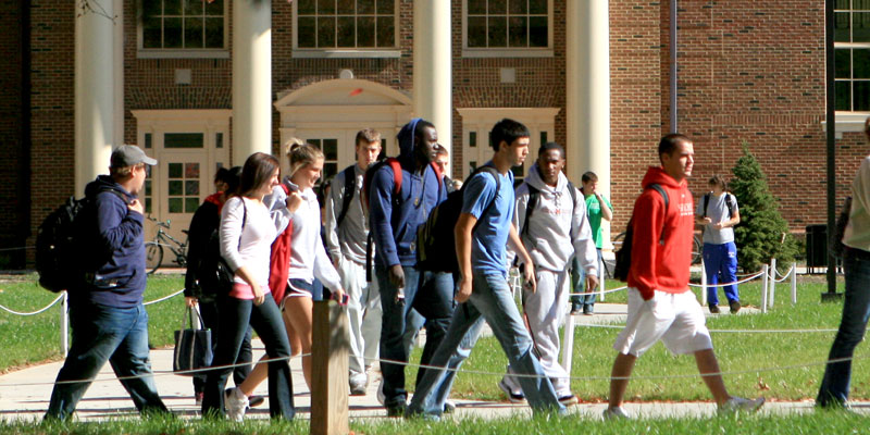 Students walking away from the Farmer School of Business with backpacks