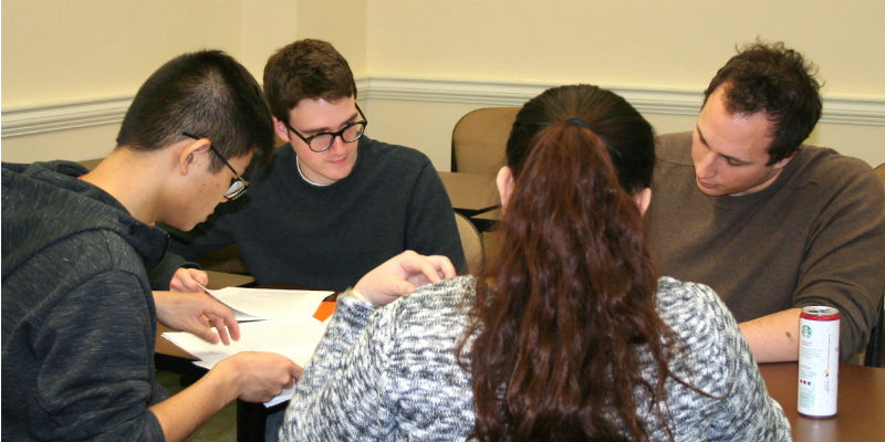 Three economic students work on and discuss economic issues in a classroom
