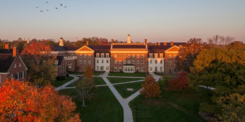 Exterior of Farmer School of Business at sunset. Brick building seen from afar with orange sunlight hitting the upper windows, shadows below as the sun sets.