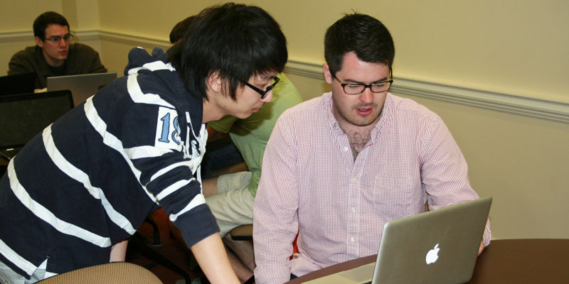 Two male students huddle around a computer to study