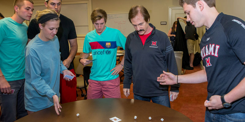 Students and professor rolling dice during an activity in entrepreneurship class